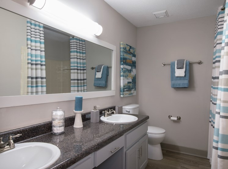 bathroom with double sinks, granite countertops, and large mirror