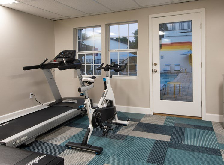 fitness center with treadmill, cardio bike, and view of pool