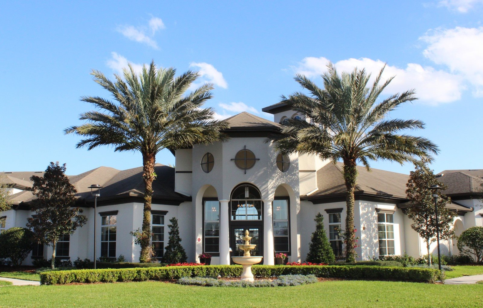 Water Mark Clubhouse with towering Palm Trees and fountain