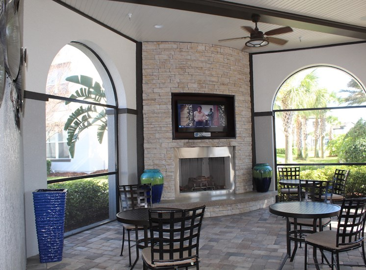 Outdoor lounge with fireplace, TV, and tables and chairs