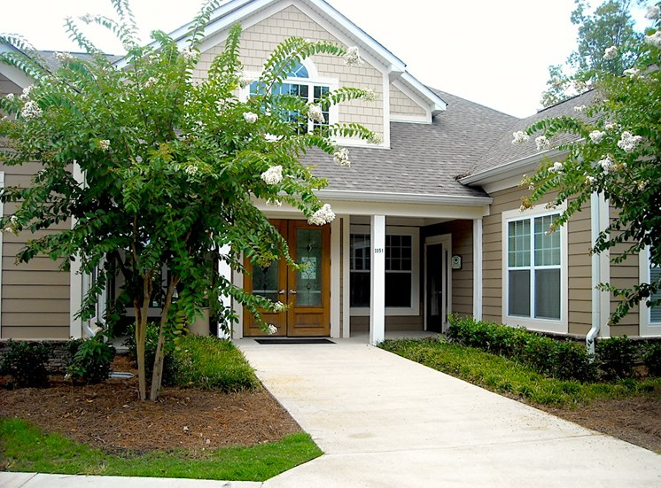 leasing office and clubhouse exterior with crepe myrtles