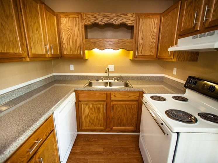 wood cabinets, white stove and dishwasher in kitchen