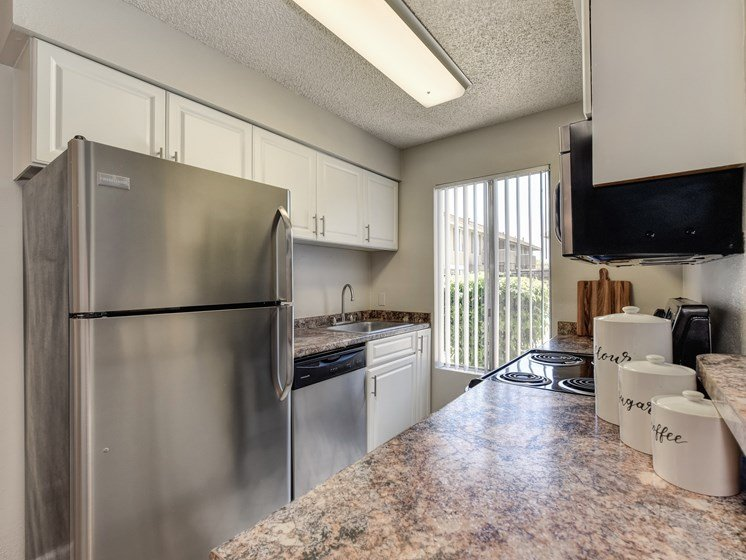 Kitchen with stainless steel appliance package, white cabinetry and ample counter space