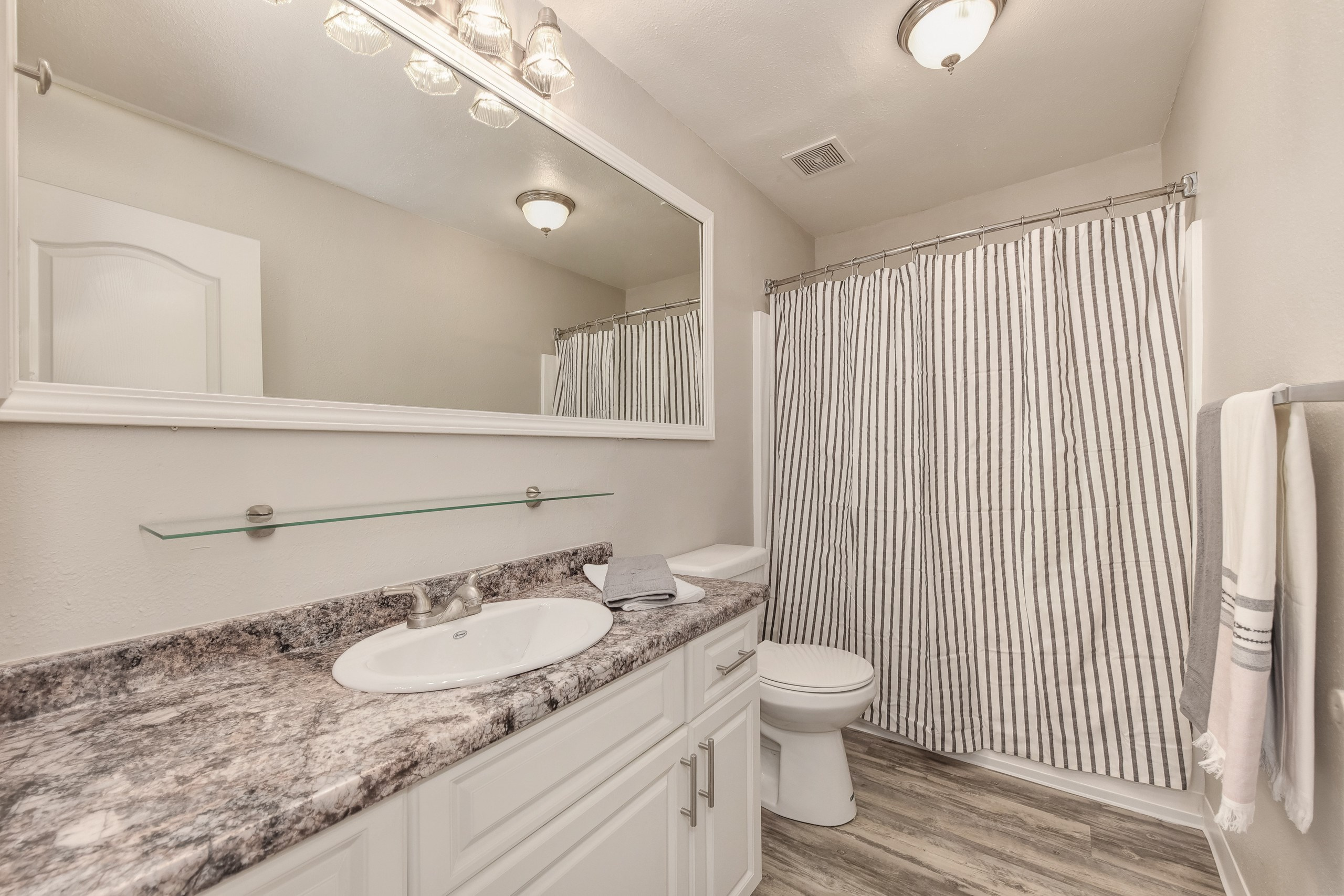 Bathroom with large mirror and white cabinetry