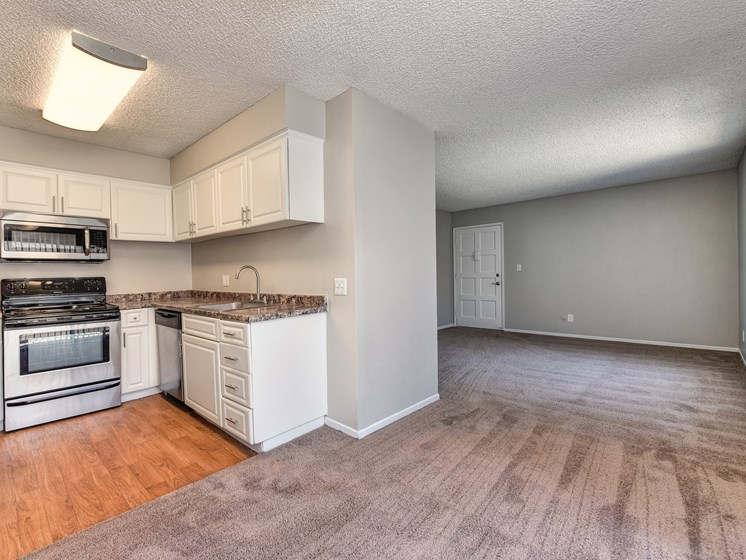 Two Bedroom Dining Room and Kitchen with wall to wall carpet, white cabinetry and stainless steel appliances