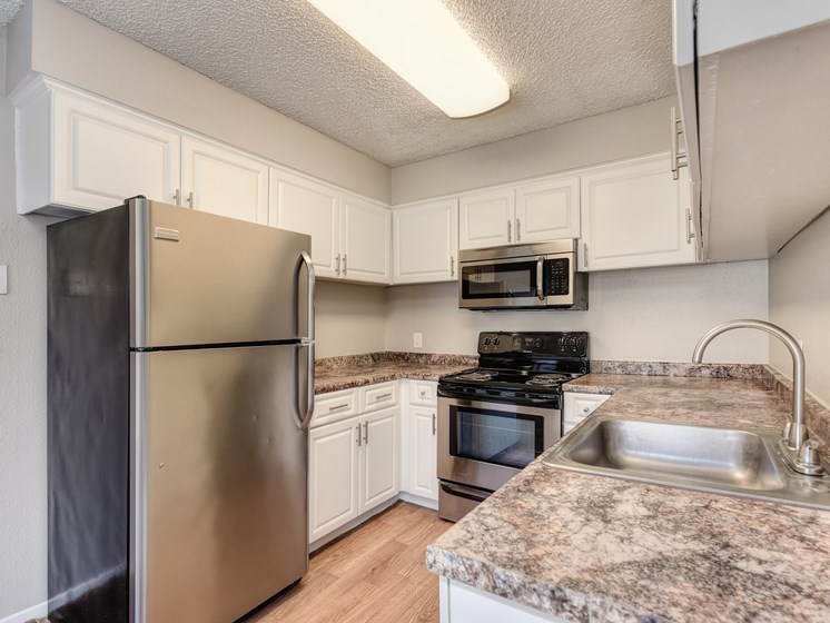 Kitchen with ample counter space, white cabinetry and stainless steel appliance package