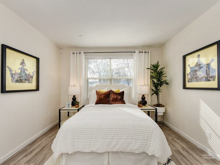 Master bedroom with large white bed positioned under the window.