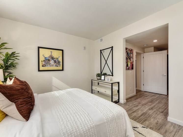 Master bedroom with large bed,  dresser/table, wall art and hardwood inspired flooring.