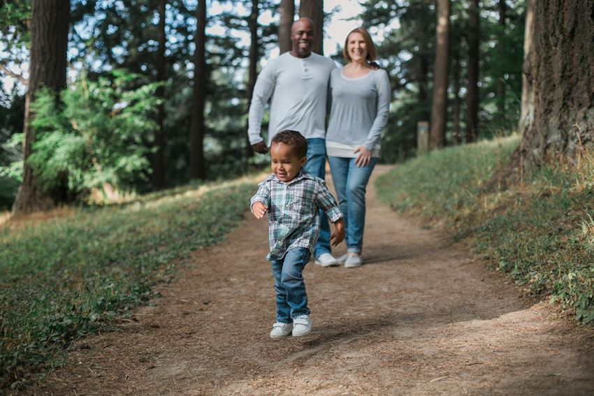 A man, woman, and child walking on a trail in a forest