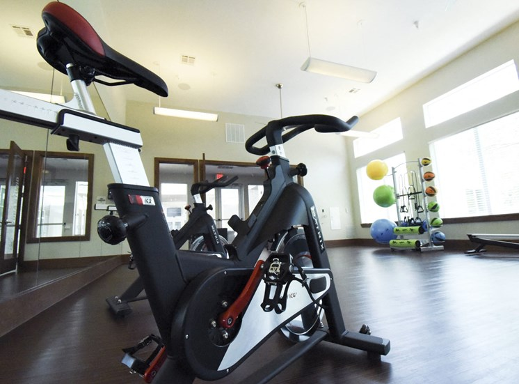 Fitness center with open floor with exercise bike and exercise balls
