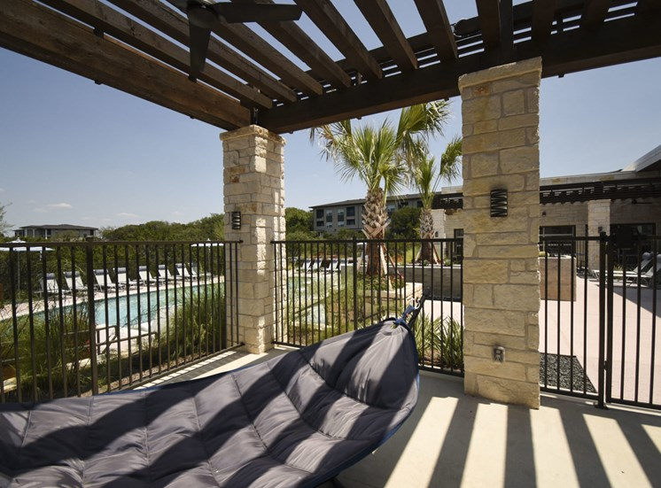 Outdoor seating area with hammock and view of pool