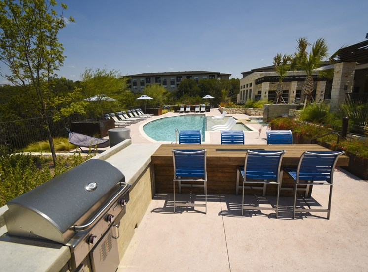 Community pool with BBQ grill and outdoor dining area