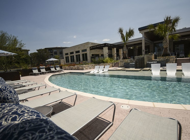 Community resort style pool with water lounger and lounge seating