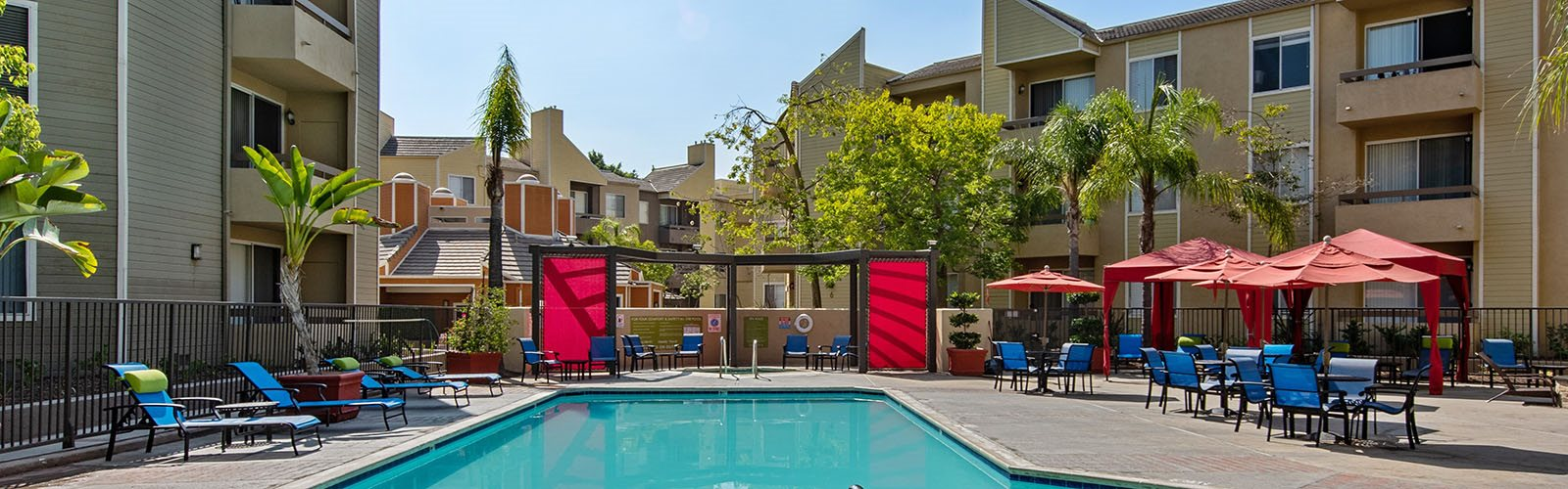 Pool with lounge chairs l  l Enclave apartments in Paramount CA