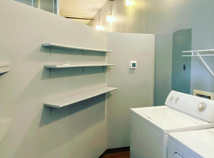 large laundry room with built-in shelving and appliances