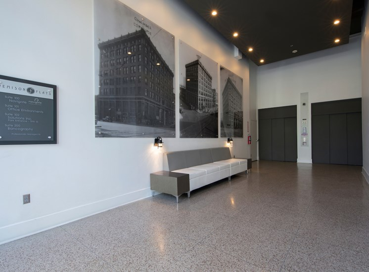 Lobby with elevators, seating, and historic photos at Jemison Flats