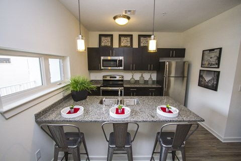 Kitchen with stainless steel appliances, dark wood cabinetry, three person seated bar and hardwood flooring