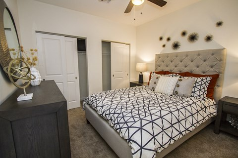 Bedroom with queen size bed, dresser, ceiling fan with light, two nightstands, and two sliding door closets