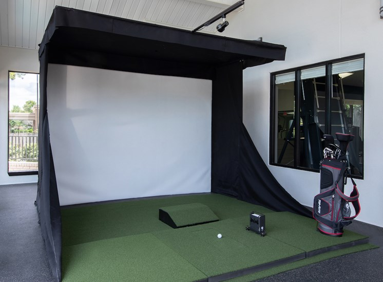 golf simulator with clubs at Reserve at Research Park