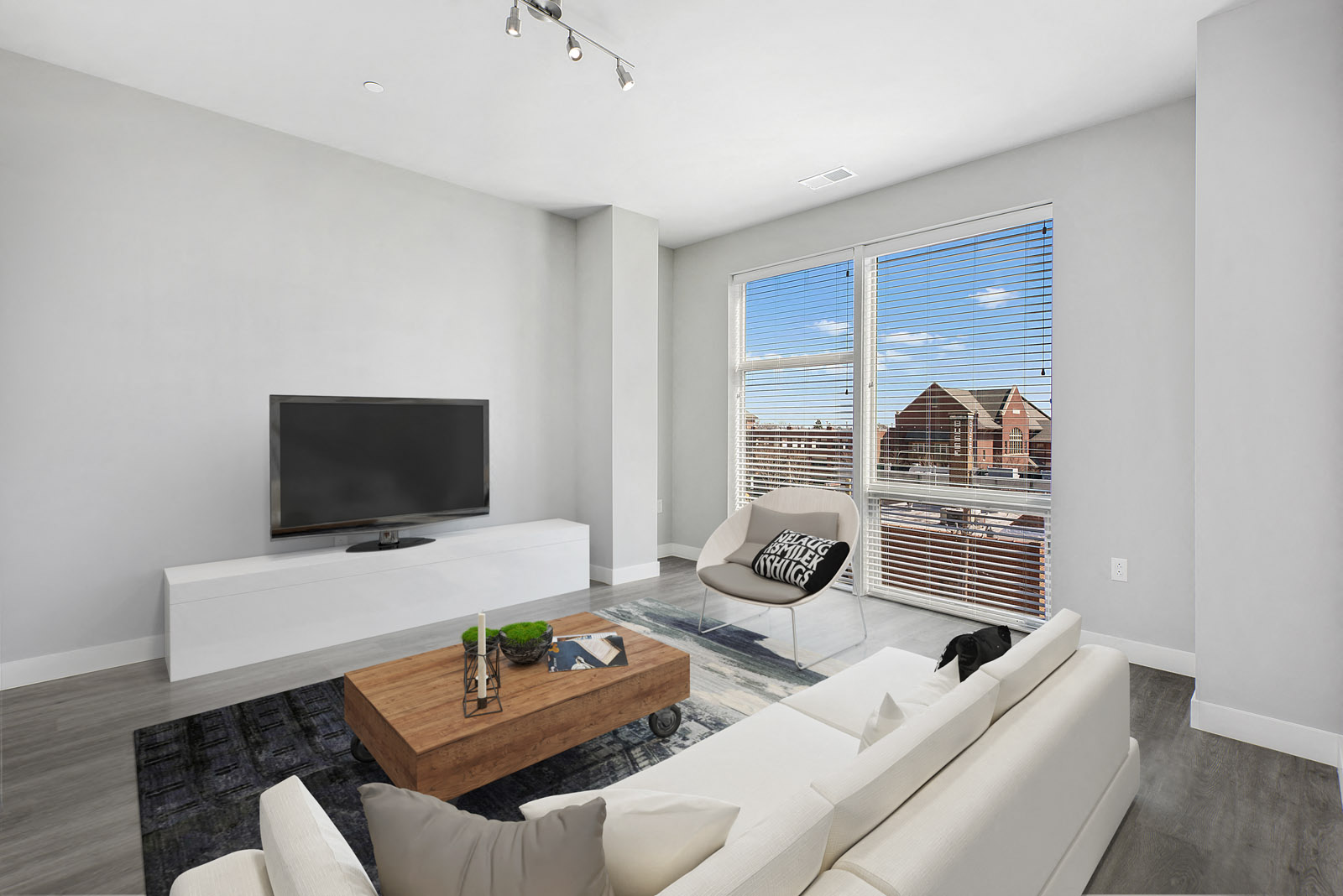 1 bedroom living room with counch and TV stand, floor to ceiling windows to the right of the TV