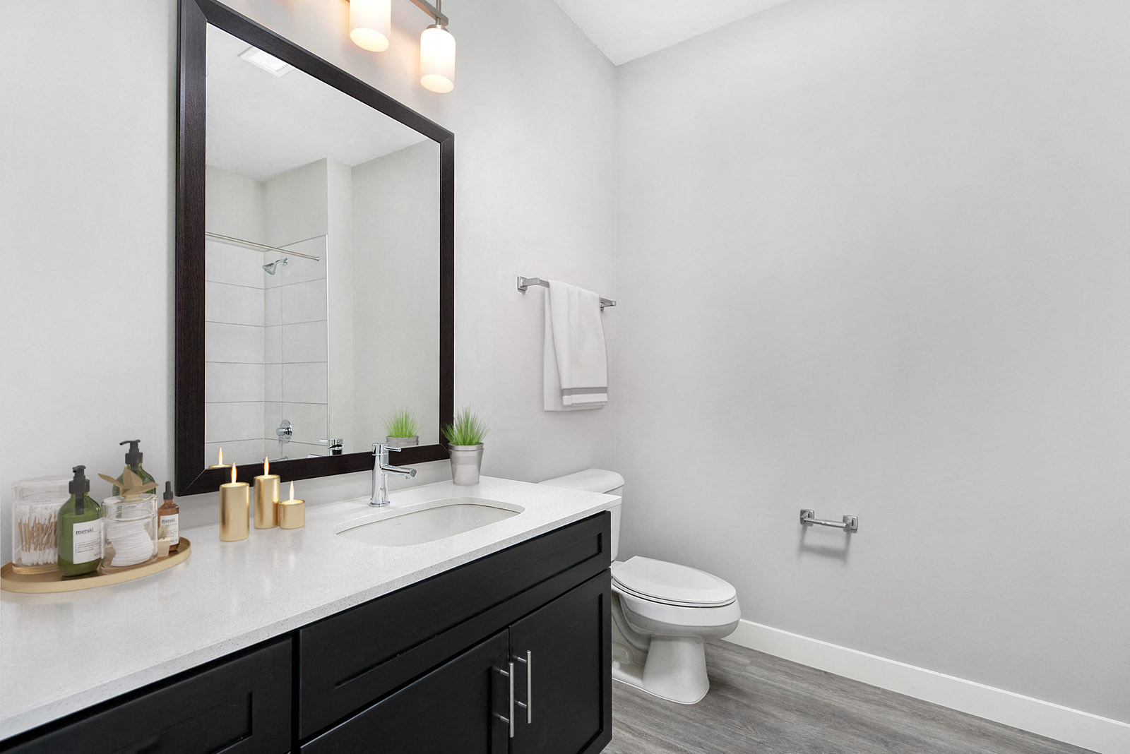 Bathroom vanity with dark cabinets, framed mirror, and tub/shower combo