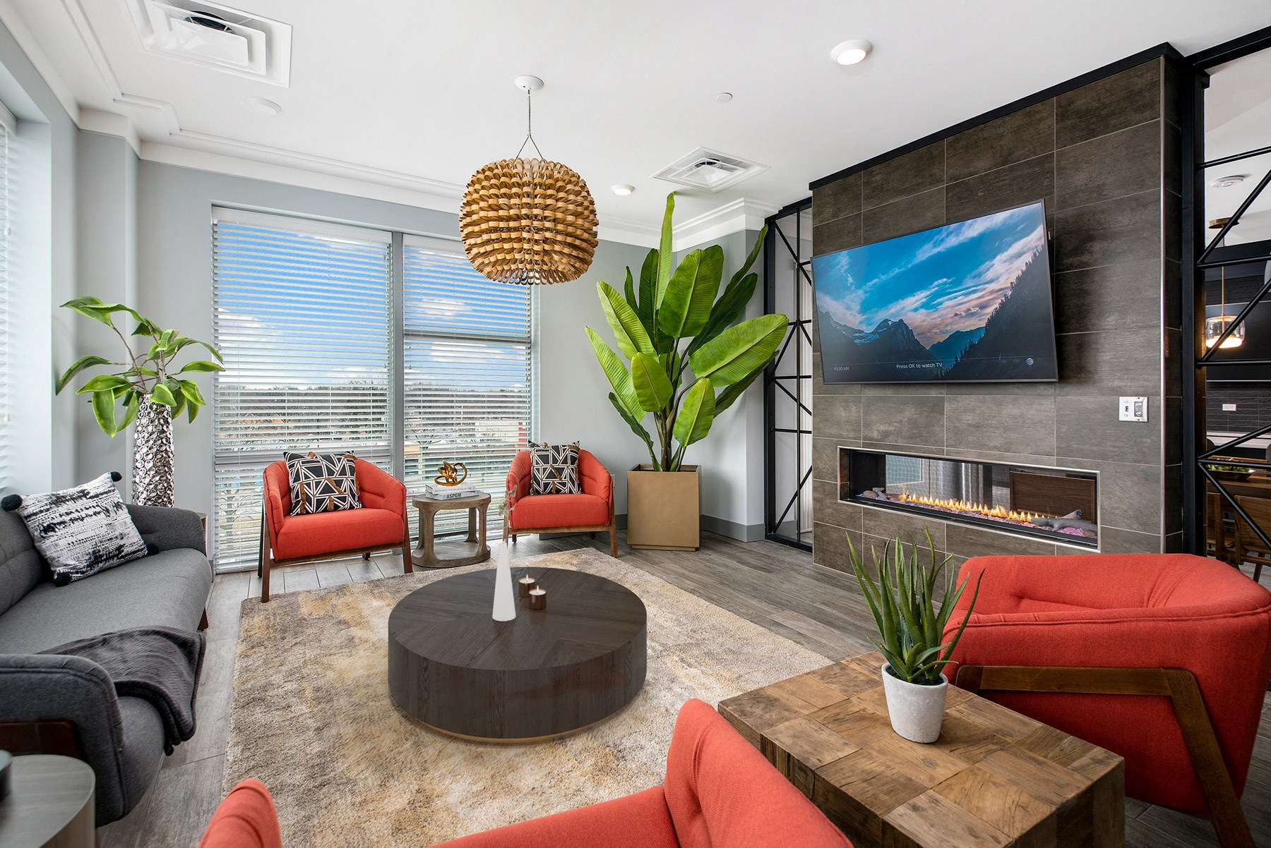 Great room with 4 red chairs, a grey couch and fireplace on the righthand side. TV above the fireplace for entertaining