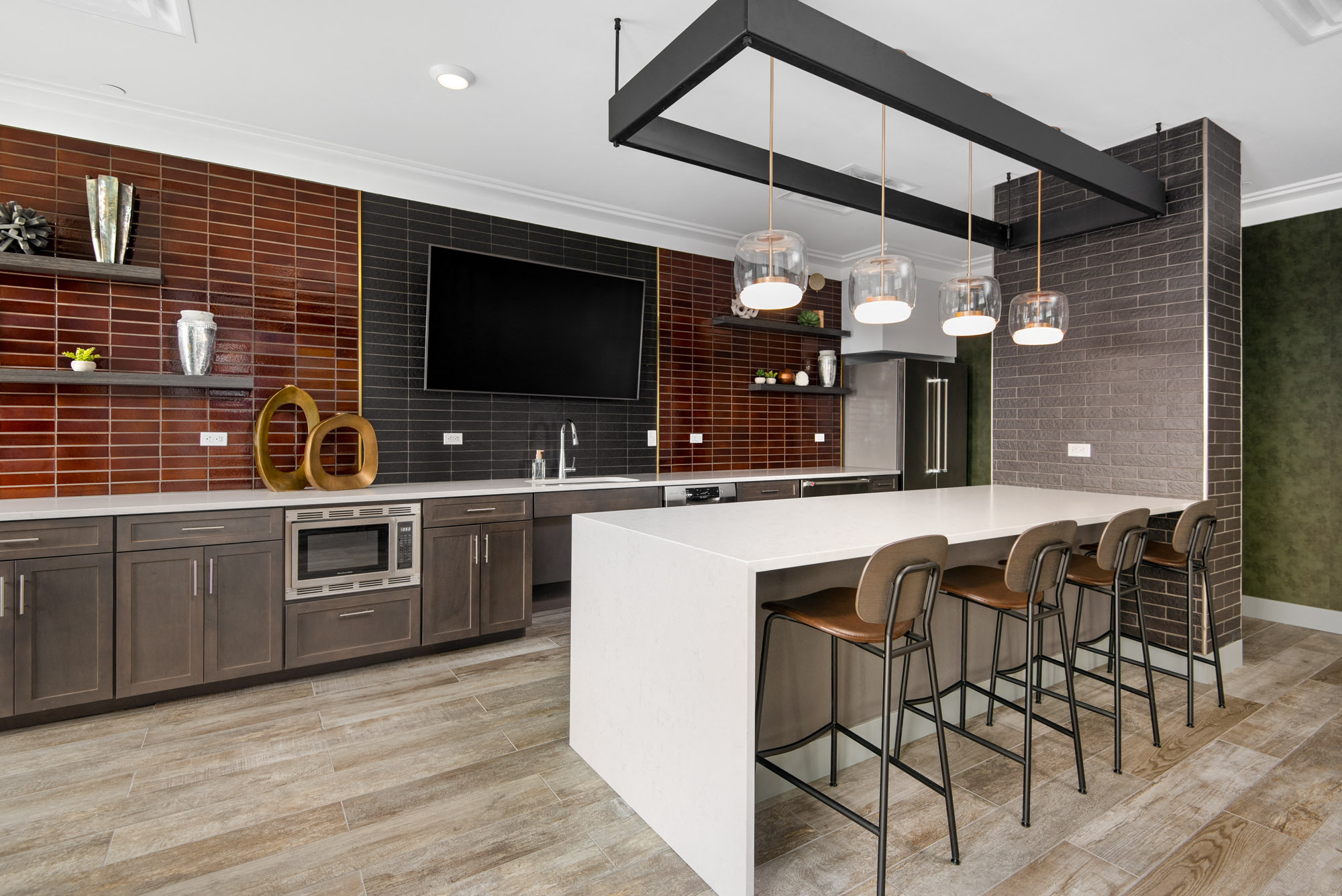 Demonstration kitchen with refrigerator, microwave, countertop, and four barstools