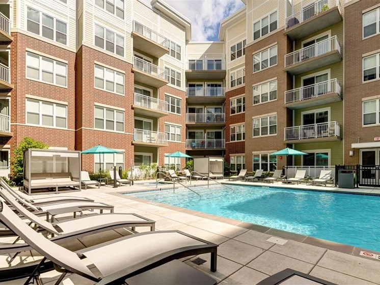 Buckingham Place Apartments Luxurious Pool with Lounge Chairs and Cabanas