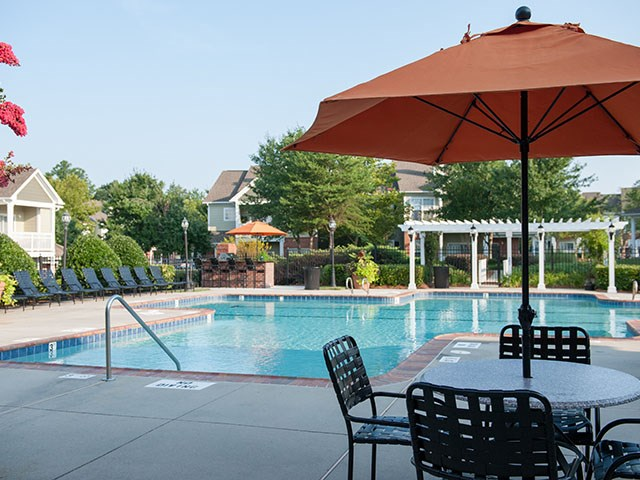 pool with chairs and table on deck at Reserve at Bridford Apartments in Greensboro