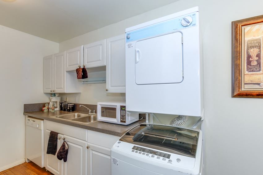 kitchen at Woodlands at Oyster Point apartments in Newport News, VA with white appliances and cabinets, stone countertops, and washer dryer unit