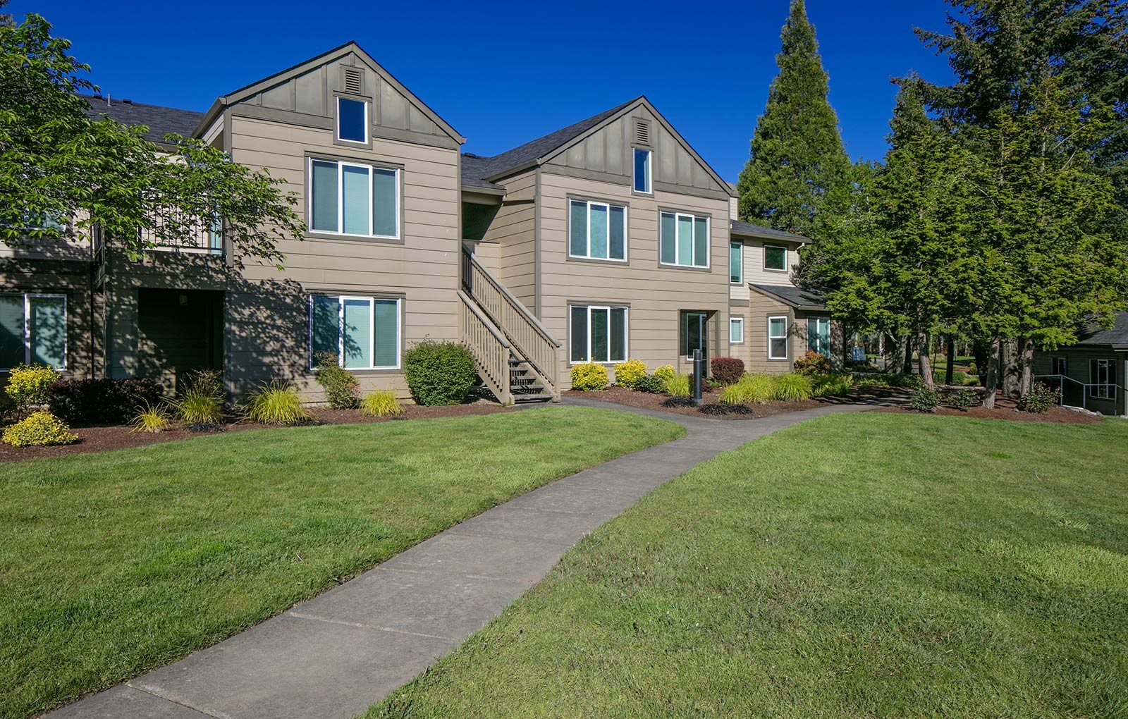 Apartment exterior with walking path at The Club apartments in Hillsboro, OR