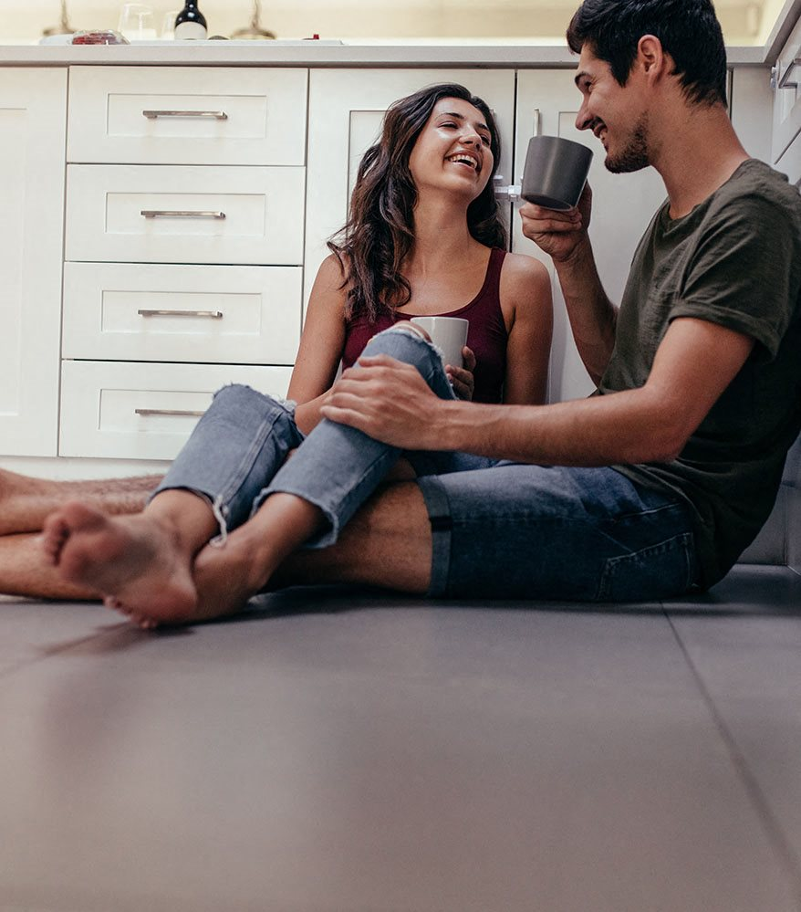 Couple sitting on kitchen floor with coffee l Las Casitas Apartments in Hisperia Ca