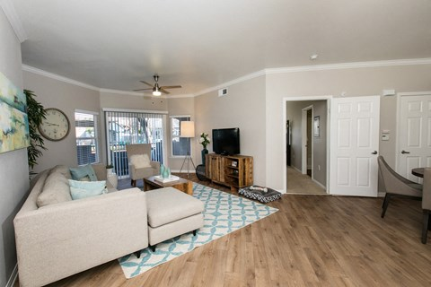 Apartments in Rancho Cordova - Avion Apartments Living Room with Wood-like Flooring, Ceiling Fan, and Access to Patio