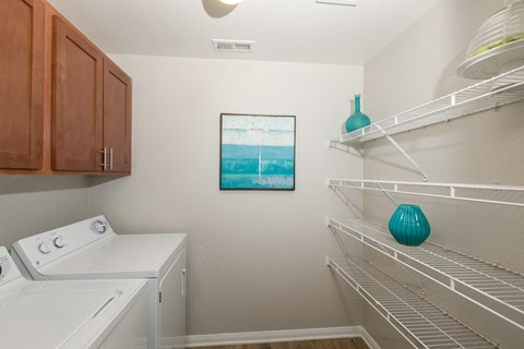 Washer dryer area with shelves l Rancho Cordova, CA Avion Apartments logo