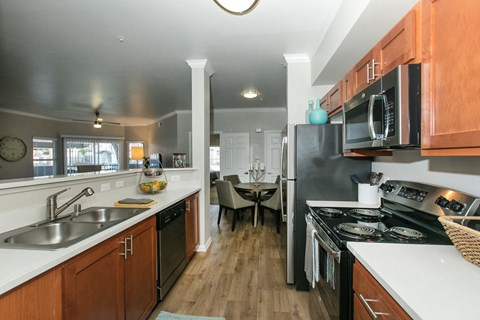 Kitchen with appliance and view of dining area l Rancho Cordova, CA Avion Apartments logo