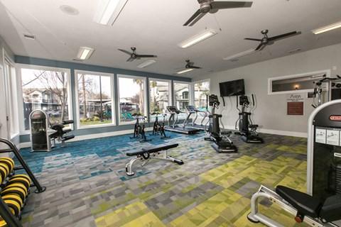 Gym with fitness equipment l Rancho Cordova, CA Avion Apartments logo