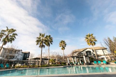 Pool with lounge chairs l Rancho Cordova, CA Avion Apartments logo