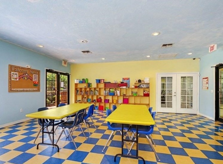 Activity Room with Blue and Yellow Tiles and Blue Chairs and Yellow Table and Shelves in the Background with Books and Bins