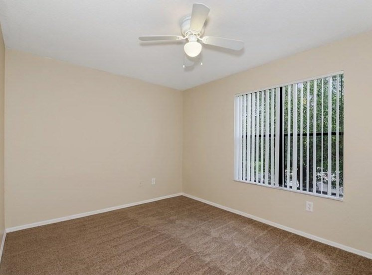 Bedroom with White Ceiling Fan and Large Window