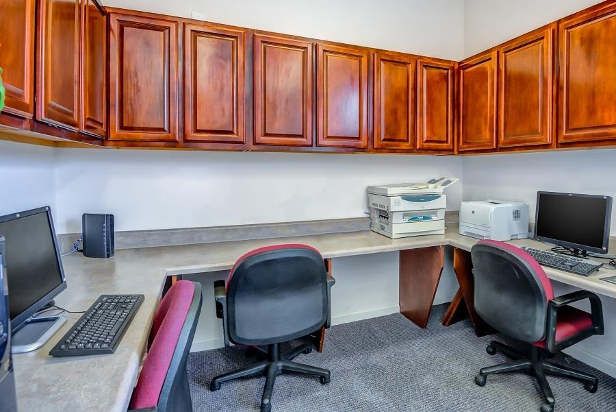 Business Center with Computers and a Printer on Grey Counter with Rolling Chairs Below Wood Cabinets