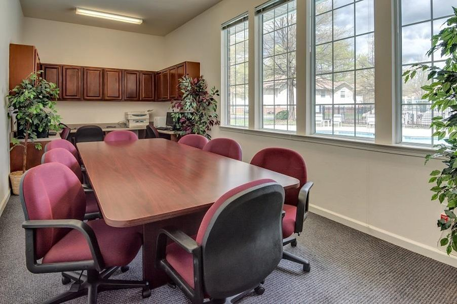 Conference Room with Large Table and Rolling Chairs Decorative Trees and Large Windows