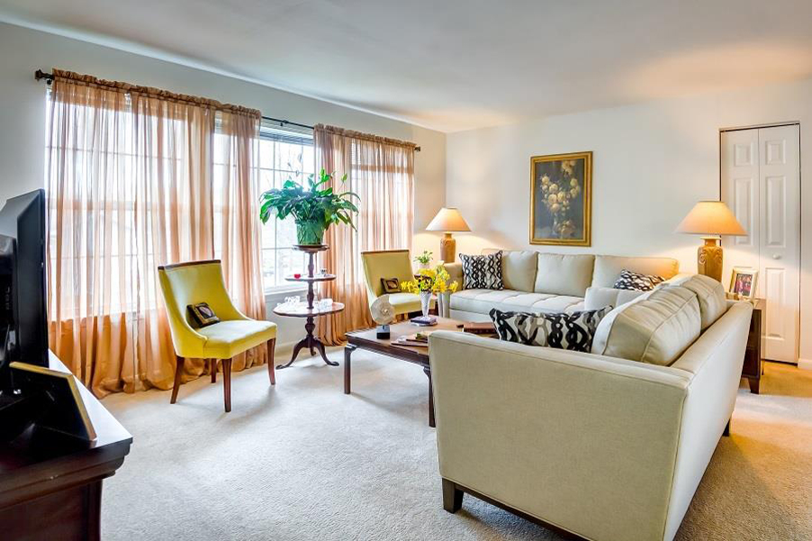 Carpeted Model Living Room with Decorations Chairs Couches and TV on Entertainment Cabinet with Large Curtain Windows in the Background