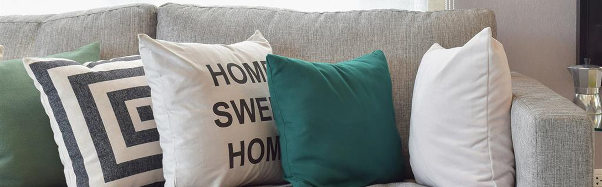 Stock Image Close up of Grey Couch with Grey Green and White Throw Pillows with Vase of White Flowers in the Foreground