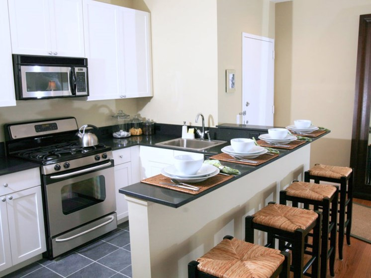 Kitchen with stainless appliances and bar with stools