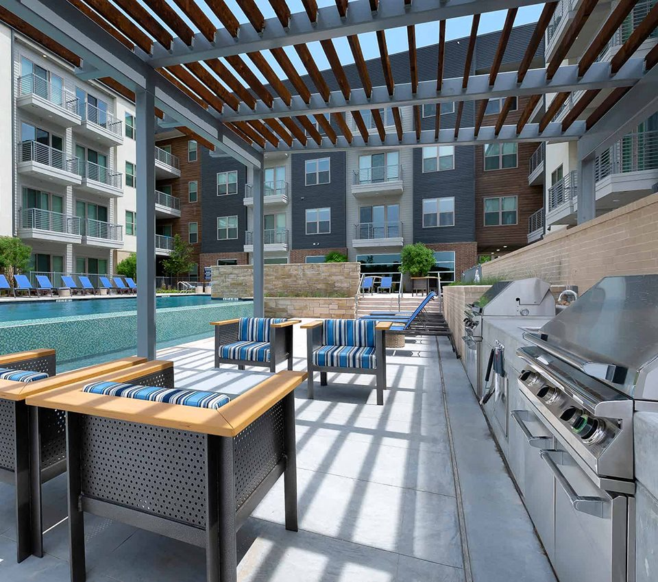 outdoor lounge with grills next to pool