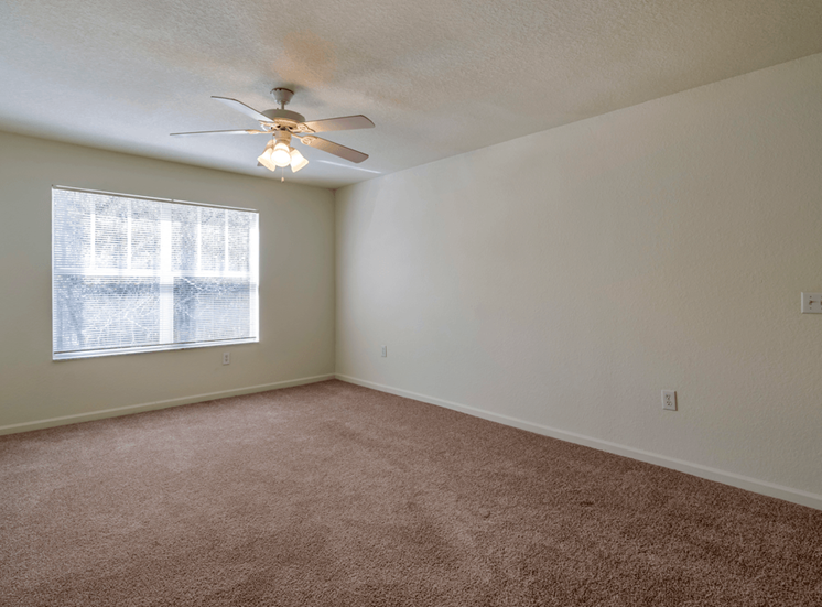 Spacious living room with carpet flooring, multi speed ceiling fan, and large window for natural lighting