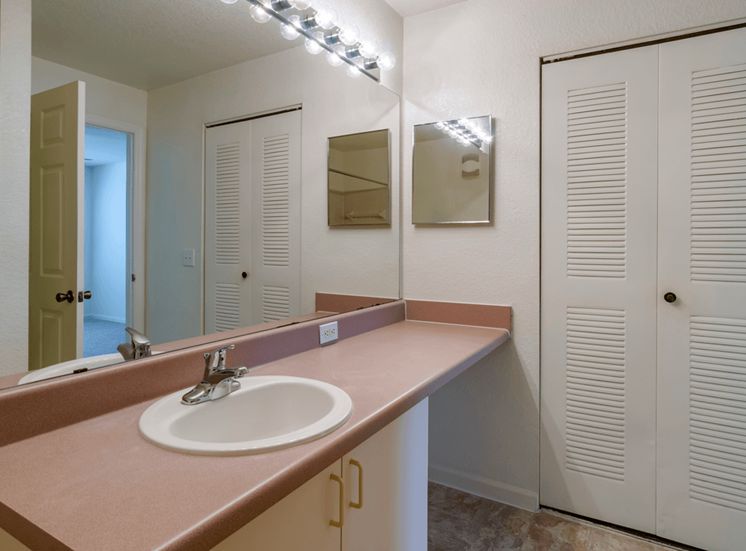 Bathroom with large mirror, vanity lighting, and large closet