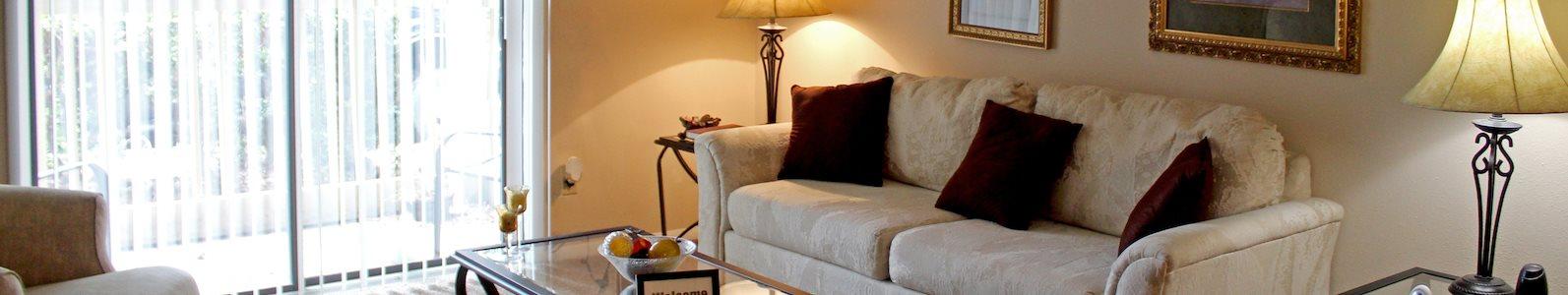 Furnished model living room with large sliding glass doors