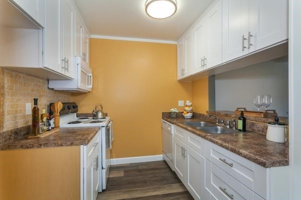 furnished kitchen with white cabinets