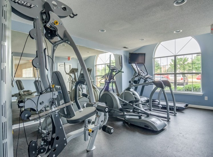 Fitness center with equipment and a mirrored wall. Window in the background and a television in the corner.